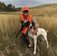 Marka Hansen posing with her dog in a field