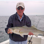Michael holding a fish in a boat on open water