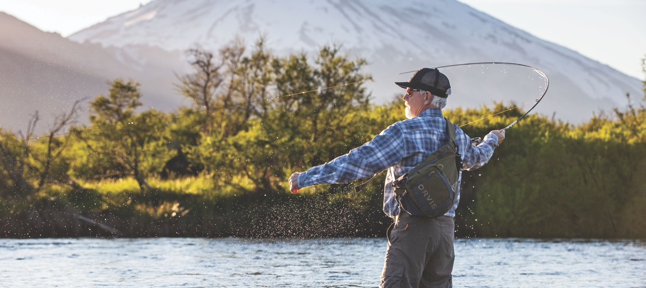 Man fly-fishing in quiet river.