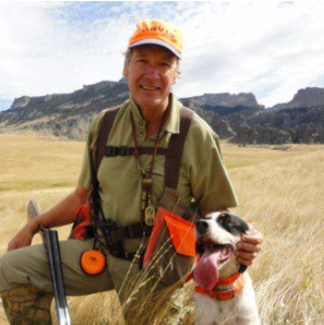 Dave Perkins in a field with a dog and shotgun