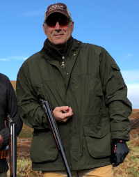 Roger N. Farah outside holding a shotgun