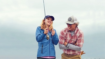 Girl recieving fly fishing instruction from her father.