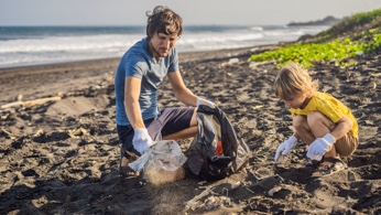 Parent and child cleaning up trash from the beach.