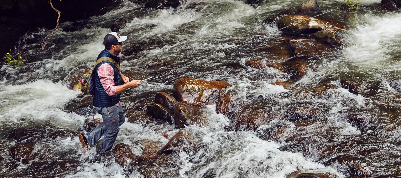 Man fly-fishing in raging river.
