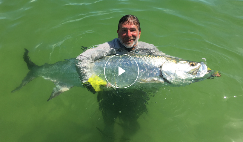 tom holding a fish | Play Video Button