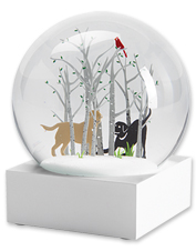 This snow globe displays two playful Labrador Retrievers frolicking in a wintry forest scene.