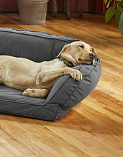 This bolster dog bed is stuffed with eco-friendly filling made from recycled plastic bottles.