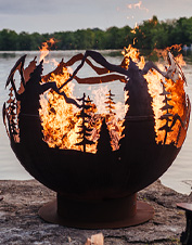 The artful Mountain Forest Fireball is a steel globe that enhances your glowing fire pit.