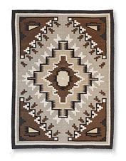 This gorgeous rug features Southwestern-inspired motifs and is loomed by hand of pure wool.